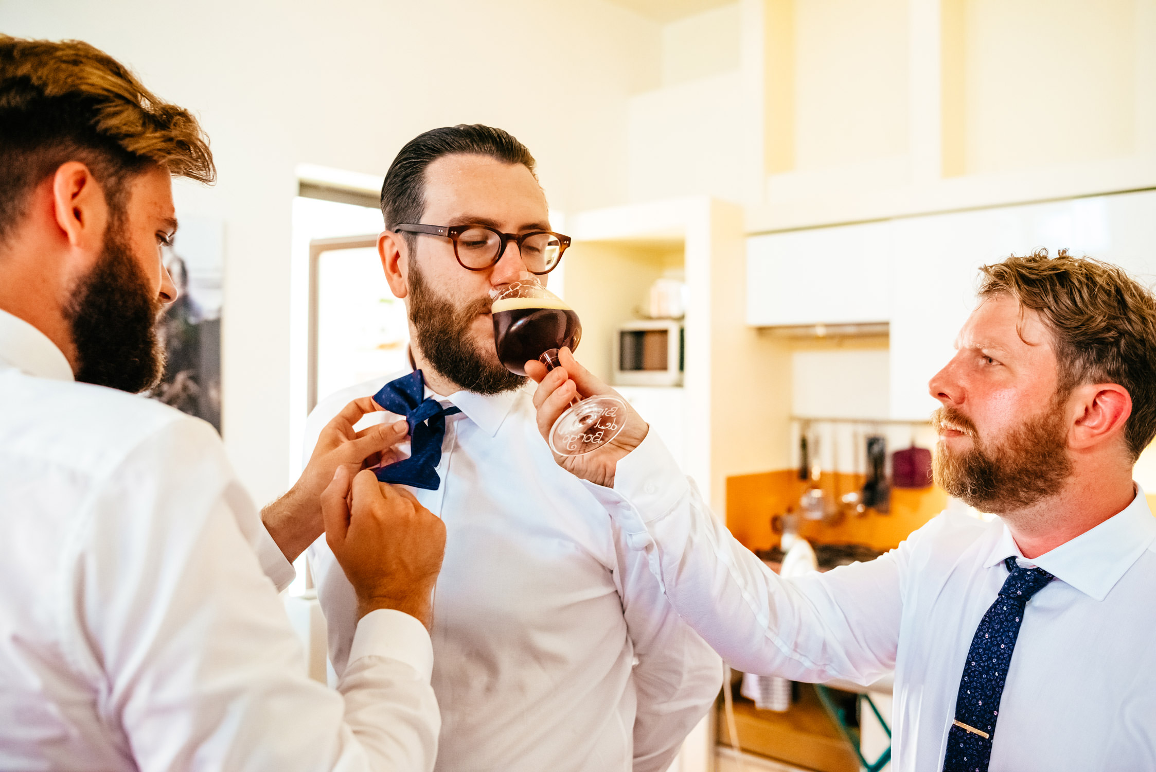 Groom getting ready with help from his groomsmen and beer before the wedding at Studi Romani Rome,Italy. Photo by destination wedding photographer Samo Rovan.